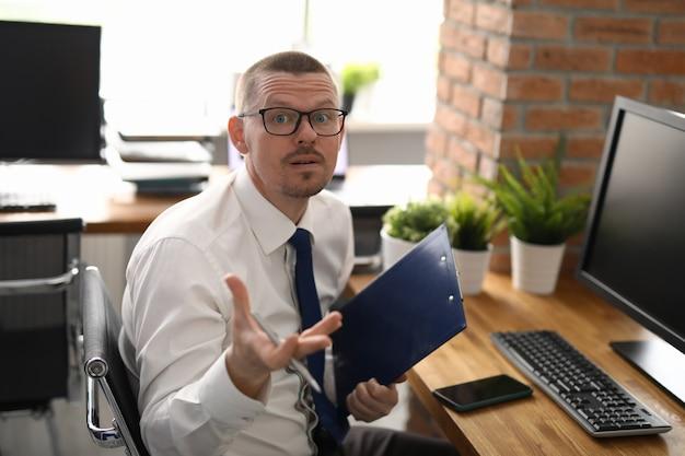 Profesjonalny menedżer siedzieć w biurze w miejscu pracy, trzymać folder z dokumentami.