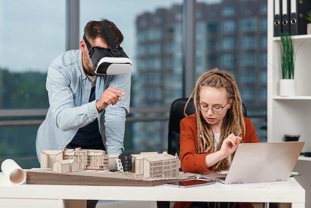 Profesjonalny męski architekt w goglach rozszerzonej rzeczywistości pracujący z makietą budynku i kobiety