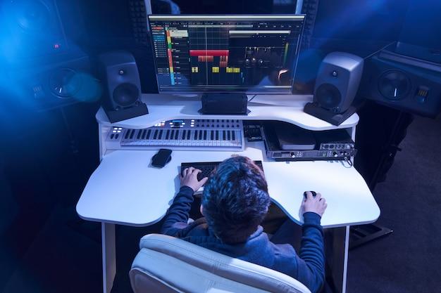 Profesjonalny męski inżynier dźwięku miksujący dźwięk w studiu nagrań. technologia produkcji muzycznej, praca na mikserze