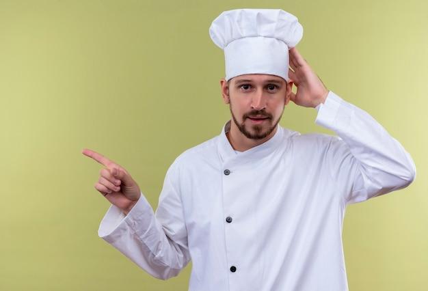 Profesjonalny męski kucharz w białym mundurze i kapeluszu kucharza dotykając kapelusza wskazując palcem wskazującym w bok z pewnym uśmiechem na twarzy stojącej na zielonym tle