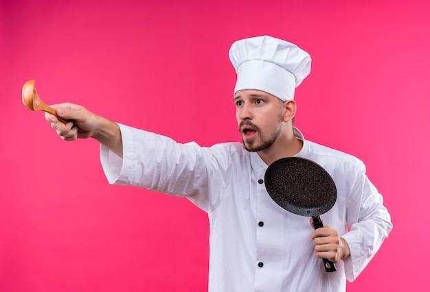 Profesjonalny męski kucharz w białym mundurze i kapeluszu kucharza trzyma patelnię, wskazując drewnianą łyżką na bok, patrząc zaskoczony i zmartwiony stojąc na różowym tle