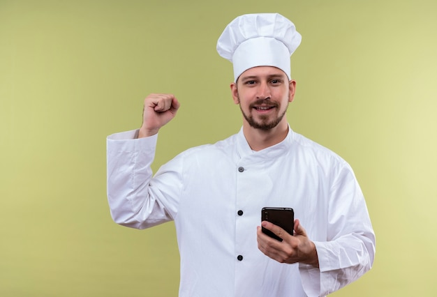 Profesjonalny męski kucharz w białym mundurze i kapeluszu kucharza trzymając telefon komórkowy podnoszący pięść szczęśliwy i pozytywny, ciesząc się swoim sukcesem stojącym na zielonym tle