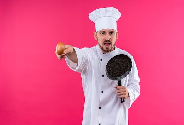 Profesjonalny męski kucharz w białym mundurze i kapeluszu kucharza trzymającego patelnię wskazującą na coś drewnianą łyżką emocjonalną i zmartwioną stojącą na różowym tle