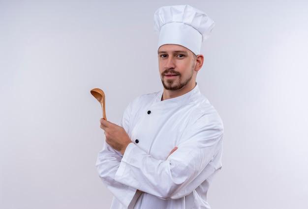 Profesjonalny mężczyzna kucharz w białym mundurze i kapelusz kucharz trzymając drewnianą łyżkę patrząc pewnie stojąc na białym tle