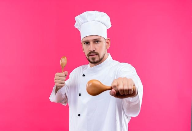 Profesjonalny mężczyzna kucharz w białym mundurze i kapelusz kucharz trzymając drewniane łyżki patrząc na kamery z poważną twarzą stojącą na różowym tle