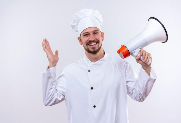 Profesjonalny mężczyzna kucharz w białym mundurze i kapelusz kucharz trzymając megafon uśmiechnięty szczęśliwy i pozytywny pozycja na białym tle