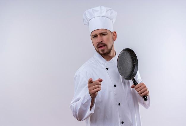Profesjonalny mężczyzna kucharz w białym mundurze i kapelusz kucharz trzymając patelnię, wskazując na aparat z pewnym siebie spojrzeniem stojącym na białym tle