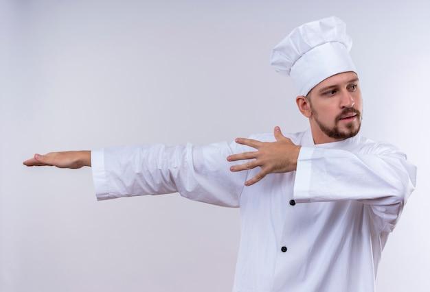 Profesjonalny mężczyzna kucharz w białym mundurze i kapelusz kucharz, wskazując rękami i rękami z boku stojącego na białym tle