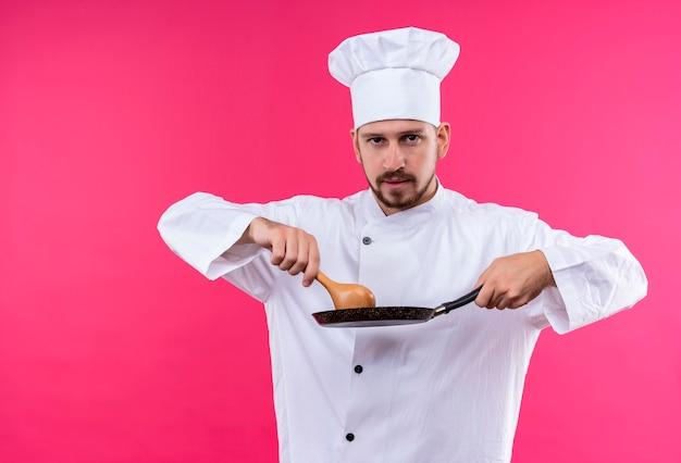 Profesjonalny mężczyzna kucharz w białym mundurze i kapeluszu kucharz trzyma patelnię i drewnianą łyżkę patrząc pewnie stojąc na różowym tle