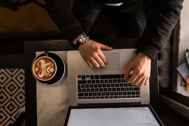 Profesjonalny mężczyzna pracujący na laptopie i pijący kawę, widok z góry