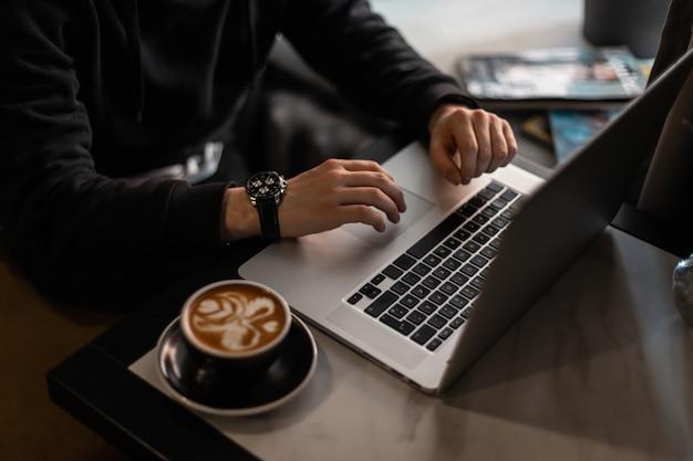 Profesjonalny mężczyzna w czarnej bluzie z luksusem pracuje godzinami przy laptopie i pije kawę cappuccino w kawiarni. freelancer pracujący w pomieszczeniu, zbliżenie