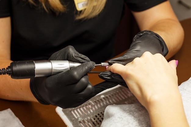 Profesjonalny mistrz manicure sprawia, że paznokcie trafiają do klienta.