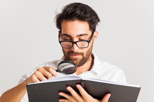 Profesjonalny młody człowiek czytanie z lupą i okularami