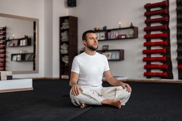 Profesjonalny młody człowiek robi joga w pomieszczeniu. medytacja i relaks.