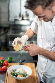 Profesjonalny młody kucharz w jednolitym tarciu świeżego sera do ceramicznej miski z sałatką składającą się z rukoli, gotowanych krewetek i innych składników