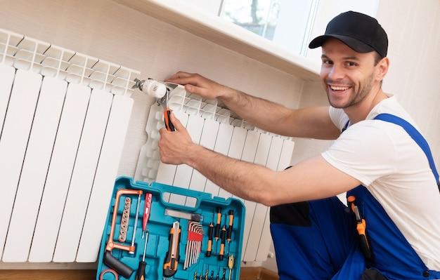Profesjonalny młody mechanik w specjalnym umundurowaniu z narzędziami montuje grzejniki i termostat w pokoju domowym