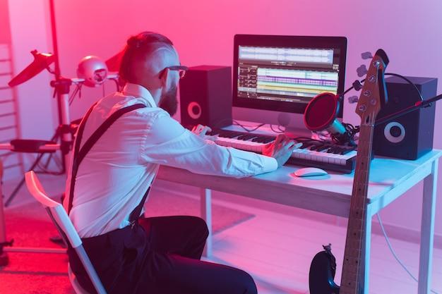Profesjonalny muzyk nagrywający syntezator w cyfrowym studio w domu, technologia produkcji muzyki