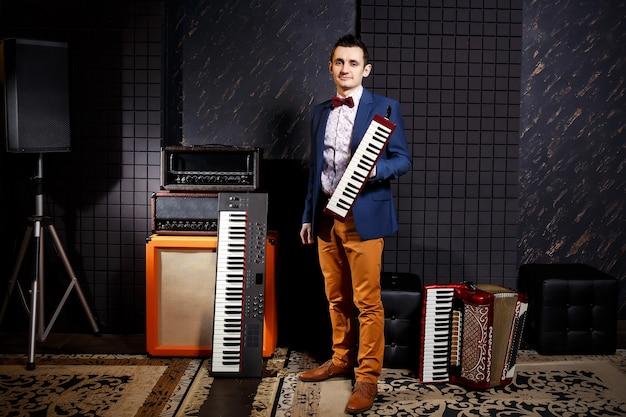 Profesjonalny muzyk posiadający studyjny syntezator klawiszowy, akordeon i harmonijkę