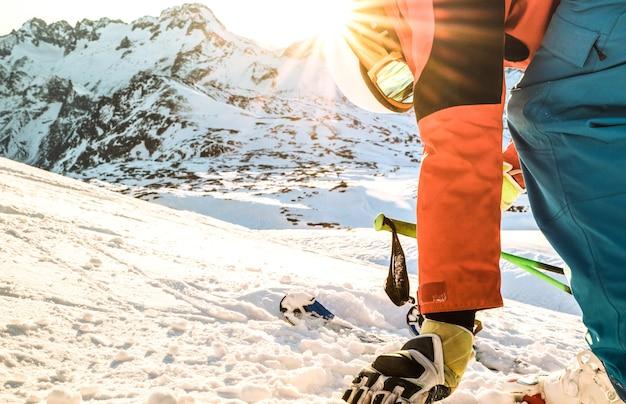 Profesjonalny narciarz o zachodzie słońca dotykający śniegu w chwili relaksu w ośrodku narciarskim we francuskich alpach