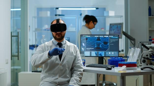 Profesjonalny naukowiec wykorzystujący innowację medyczną w laboratorium w okularach wirtualnej rzeczywistości, gestykulujący. zespół badaczy pracujących z urządzeniami, przyszłością, medycyną, opieką zdrowotną, wizją, symulatorem