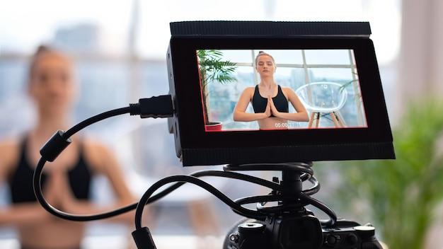 Profesjonalny operator kamery z kamerą i zewnętrznym wyświetlaczem nagrywający młodą blondynkę