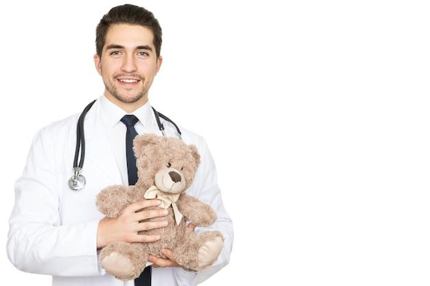 Profesjonalny pediatra. studio portret młodego przystojnego lekarza płci męskiej, trzymając misia uśmiechnięty na białym tle