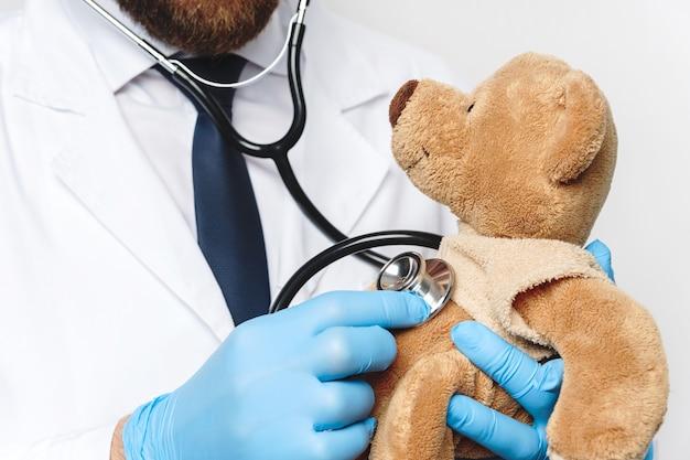 Profesjonalny pediatra z misiem w rękach na szarej ścianie