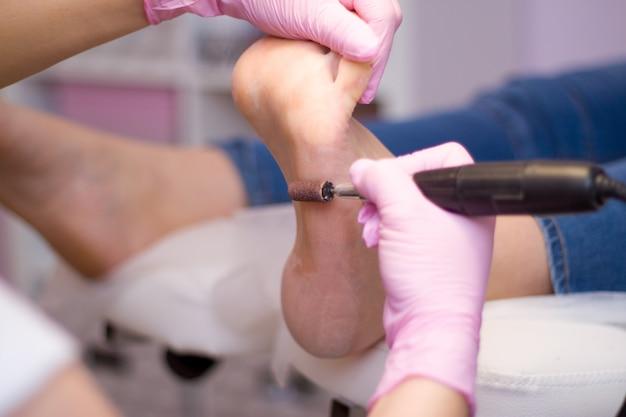 Profesjonalny pedicure sprzętowy przy użyciu różowych rękawiczek i urządzenia elektrycznego.