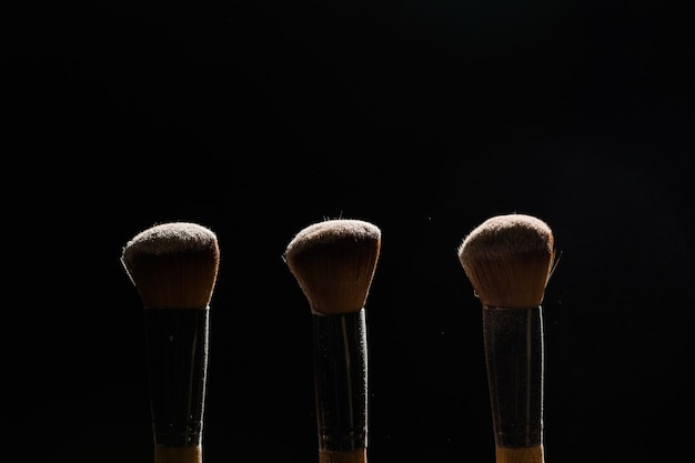 Profesjonalny pędzel do makijażu z pudrem na czarnym tle