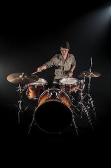 Profesjonalny perkusista grający na perkusji ustawionej na scenie na czarnym tle z pałeczkami perkusyjnymi i wyglądem vintage. widok z góry. efekt dymu