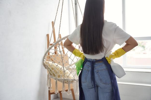 Profesjonalny płyn do mycia okien. widok z tyłu młodej kobiety, sprzątaczki w żółtych gumowych rękawiczkach, trzymając szmatę i spray podczas czyszczenia dużego okna w domu. koncepcja usług sprzątania i sprzątania