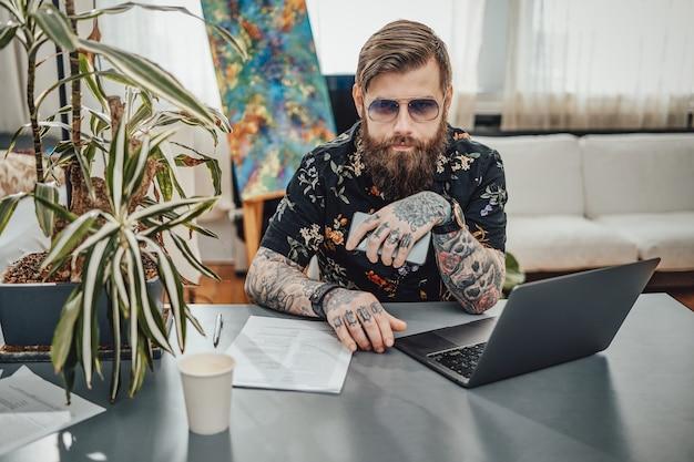 Profesjonalny portret stylowego programisty wykonującego swoją pracę za pomocą laptopa i telefonu komórkowego. praca zdalna i domowy styl życia.