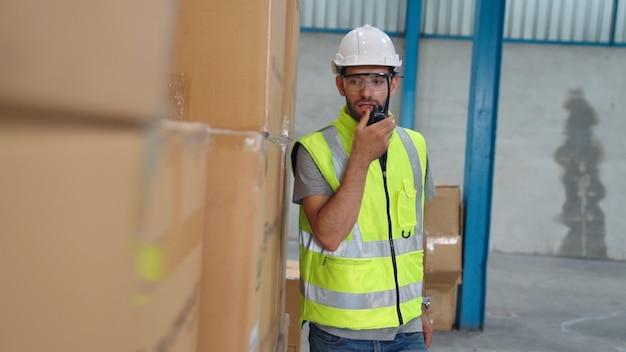 Profesjonalny pracownik ładunków rozmawia przez przenośne radio, aby skontaktować się z innym pracownikiem. koncepcja komunikacji fabryki i magazynu.