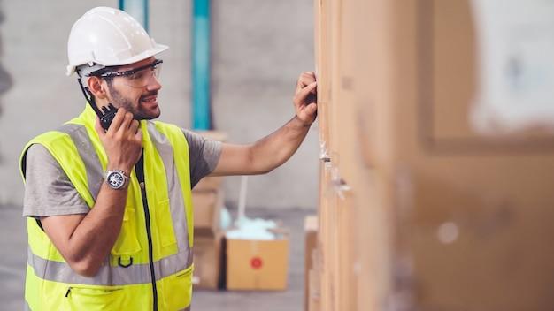 Profesjonalny pracownik ładunków rozmawia przez przenośne radio, aby skontaktować się z innym pracownikiem