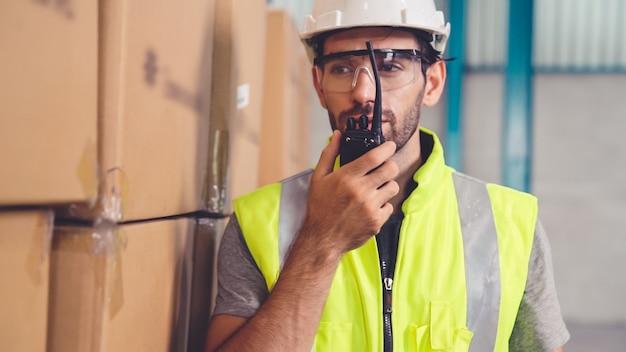 Profesjonalny pracownik ładunkowy rozmawia przez przenośne radio, aby skontaktować się z innym pracownikiem