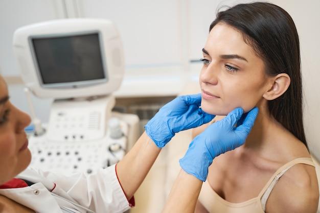 Profesjonalny pracownik medyczny stojący przed pacjentem podczas sprawdzania tarczycy