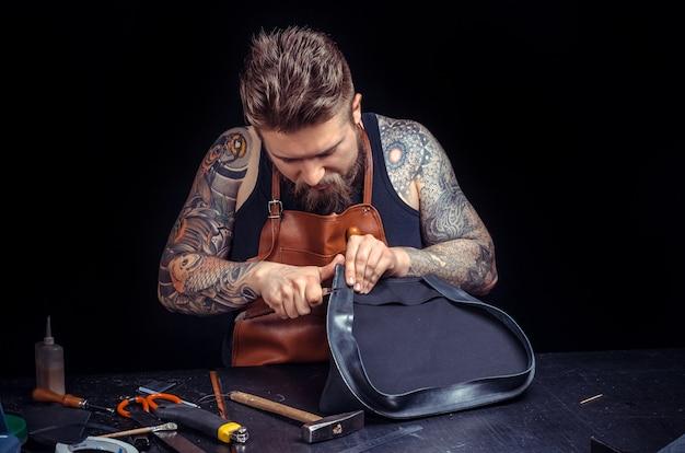 Profesjonalny pracownik skórzany produkujący wyroby skórzane przy biurku.