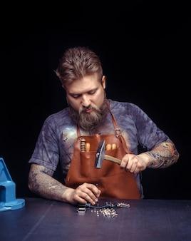 Profesjonalny pracownik skórzany produkuje galanterię skórzaną w warsztacie.