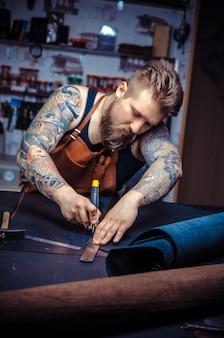 Profesjonalny pracownik skórzany wycinający galanterię skórzaną w swoim miejscu pracy.