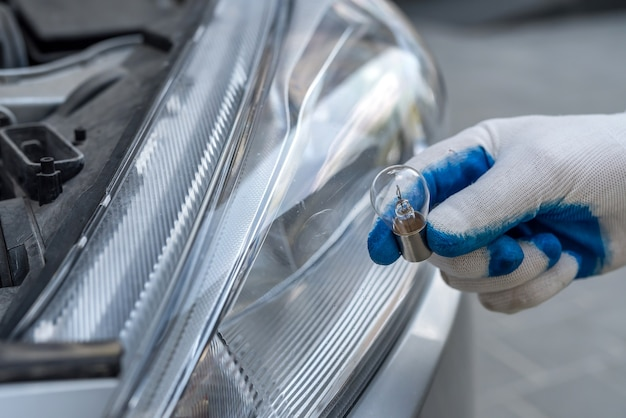 Profesjonalny pracownik zmieniający samochód na nowe żarówki halogenowe