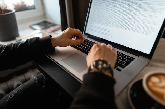 Profesjonalny programista facet freelancer pracujący na laptopie i pijący kawę w kawiarni