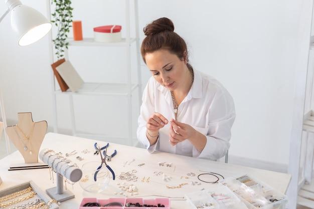 Profesjonalny projektant akcesoriów wykonujący ręcznie robioną biżuterię w pracowni. moda, kreatywność i koncepcja rękodzieła.