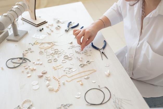 Profesjonalny projektant biżuterii, co ręcznie robiona biżuteria w studio warsztat z bliska. moda, kreatywność i ręcznie robiona koncepcja