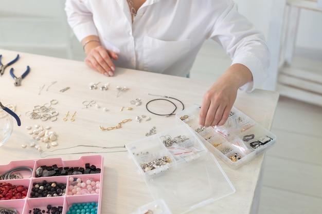 Profesjonalny projektant biżuterii, co ręcznie robiona biżuteria w warsztacie studyjnym z bliska. moda, kreatywność i ręcznie robiona koncepcja