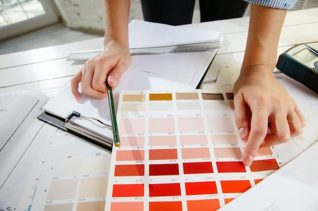 Profesjonalny projektant wnętrz lub architekt pracujący z paletą kolorów, rysunkami pomieszczeń w nowoczesnym biurze. młoda modelka planująca przyszłe mieszkanie lub dom, wybierając kolory i pochodzenie.