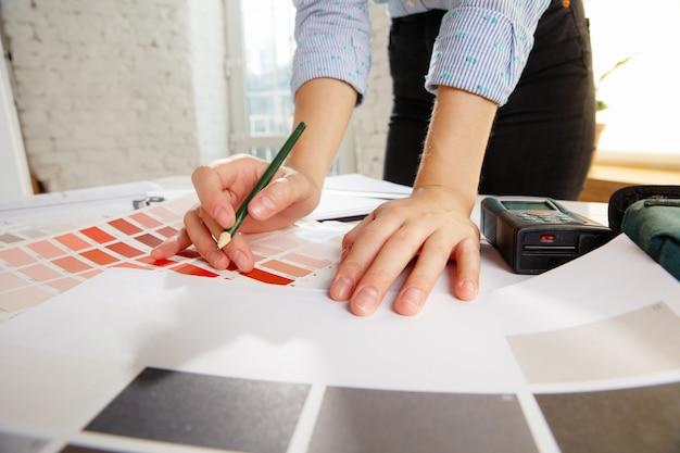 Profesjonalny projektant wnętrz lub architekt pracujący z paletą kolorów, rysunkami pomieszczeń w nowoczesnym biurze.