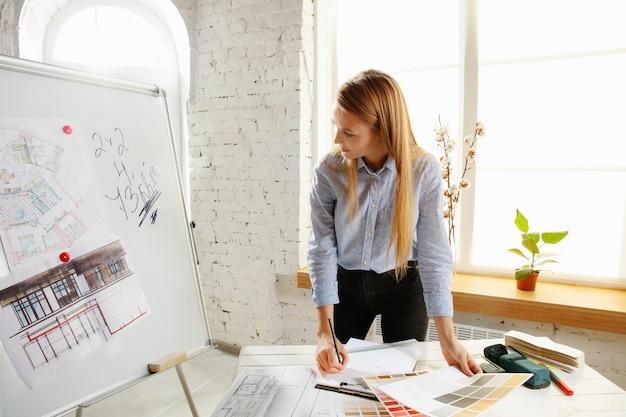 Profesjonalny projektant wnętrz lub architekt pracujący z paletą kolorów, rysunkami pomieszczeń w nowoczesnym biurze