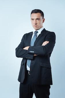 Profesjonalny przedsiębiorca. poważny, inteligentny miły biznesmen krzyżujący ramiona i patrząc przed siebie, stojąc na niebieskim tle