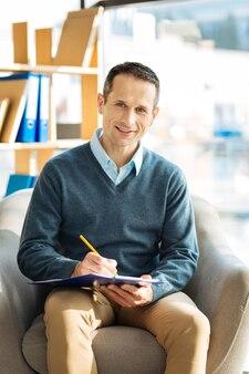 Profesjonalny psycholog. wesoły szczęśliwy miły człowiek siedzi w fotelu i robi notatki podczas pracy jako psycholog