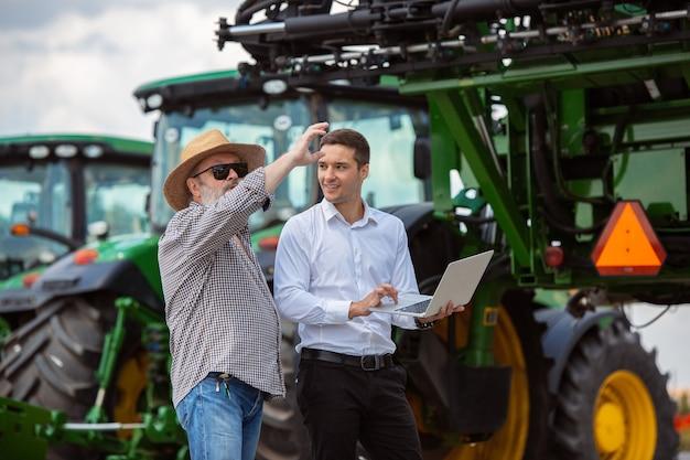 Profesjonalny rolnik z nowoczesnym kombajnem na polu w słońcu przy pracy